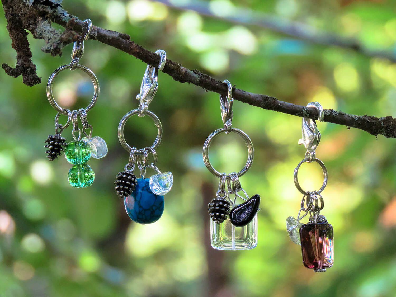 Asustekoruissa on papukaijalukko sekä avainlenkki. Koristeena kaikissa on pisarahelmi ja pikkukäpy. Koruja on neljässä värissä.