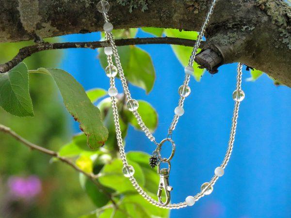Kirkkaista helmistä valmistettu avainkoru. Korussa on pieni käpy-riipus. Avain kiinnitetään papukaijalukolla.