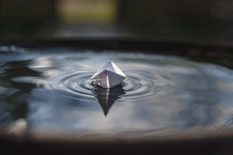 Paperista taiteltu vene vedessä.