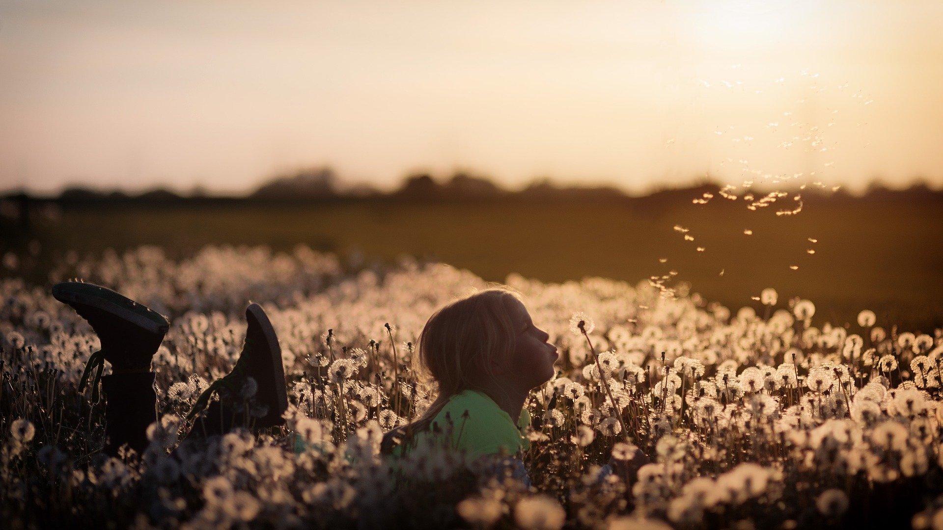 Tyttö makaa niityllä.