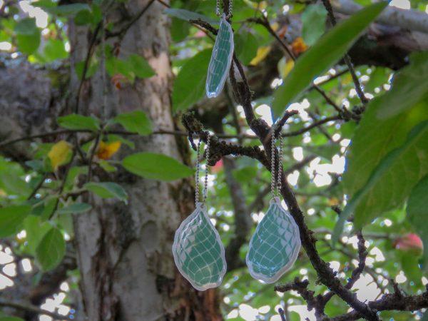 Heijastimia roikkuu puussa. Heijastimessa kuvana KÄPY ry:n logon vihreä käpy.
