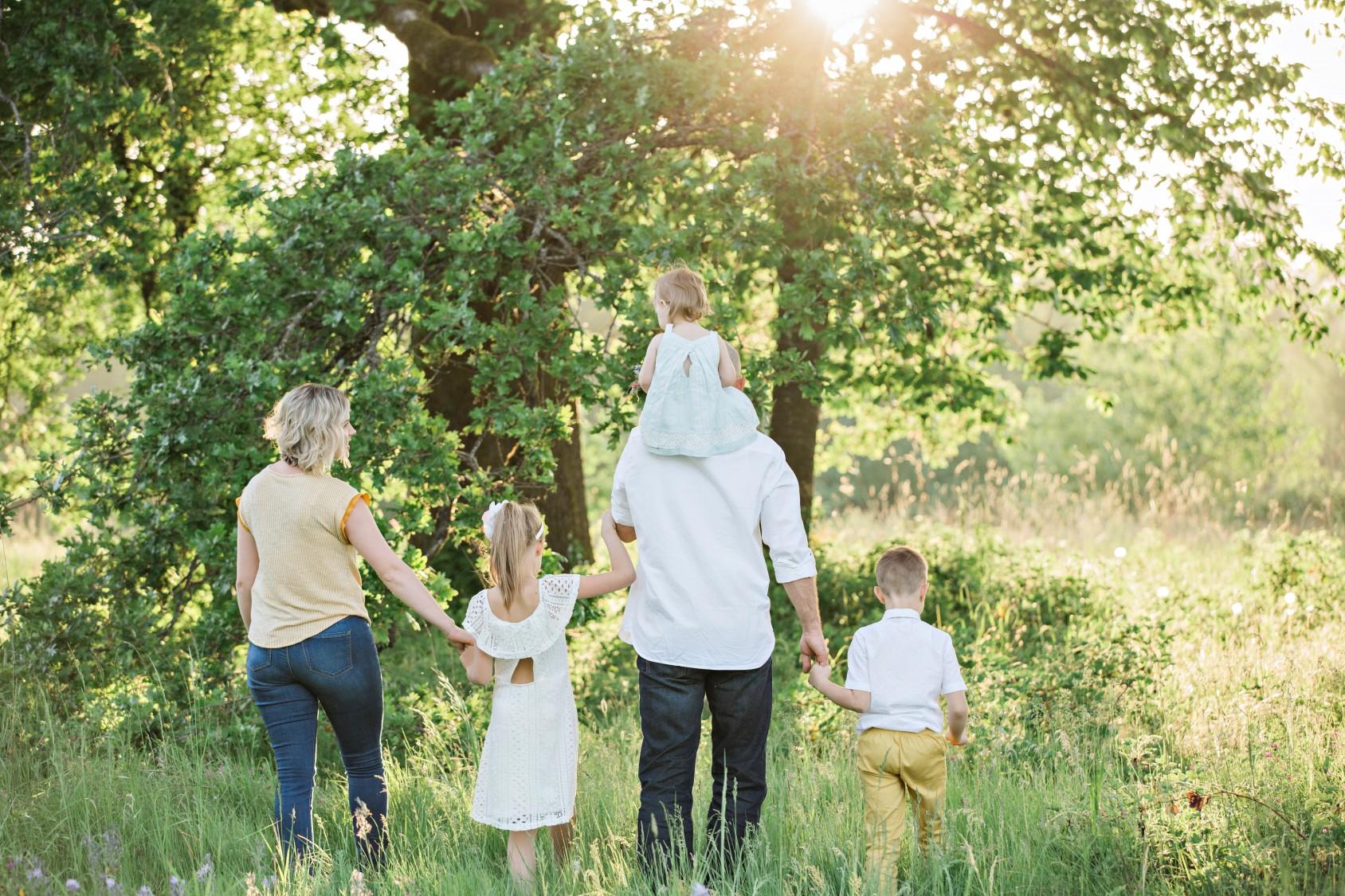 Perhe kävelee auringonpaisteessa.