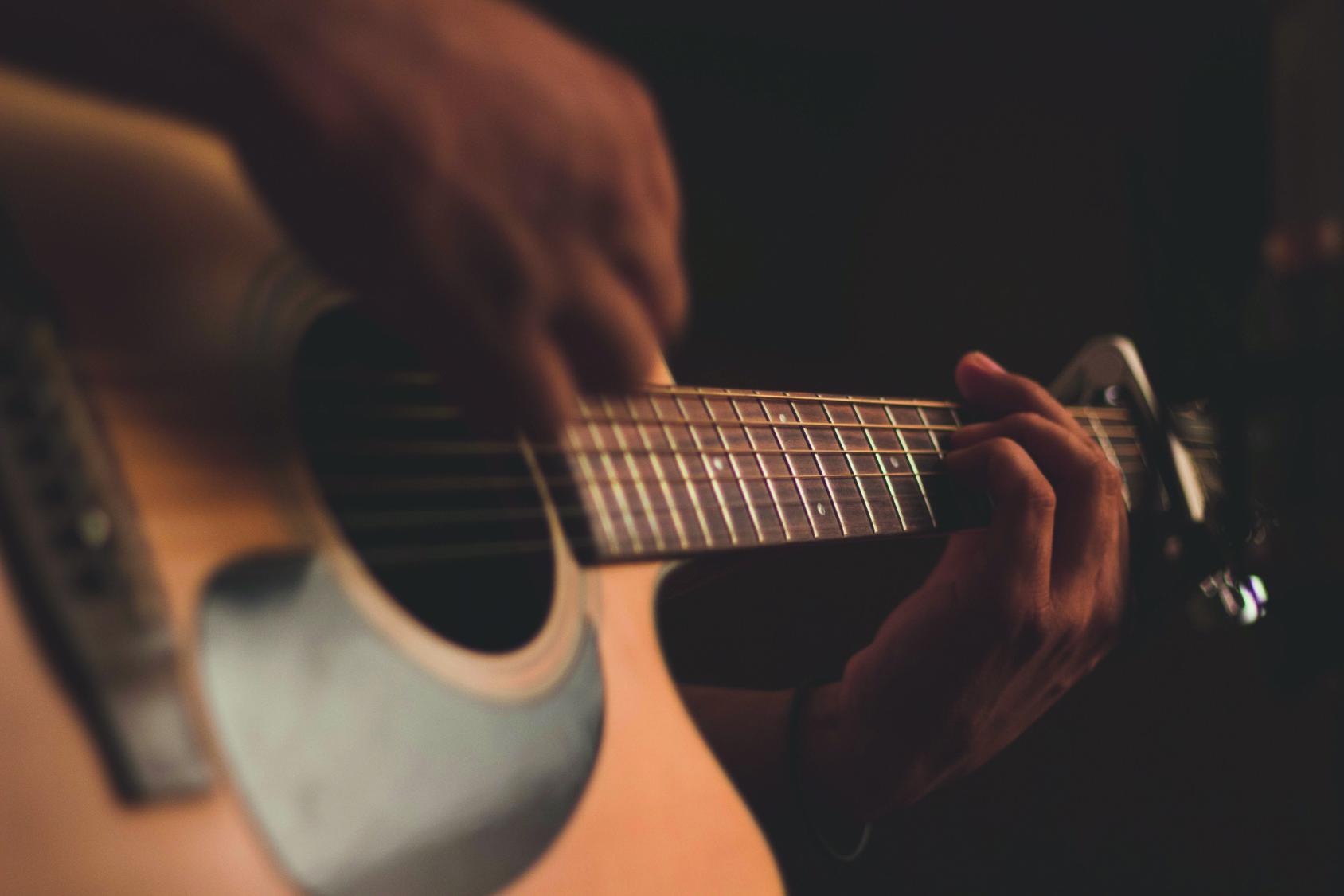 Kitara soittajan käsissä