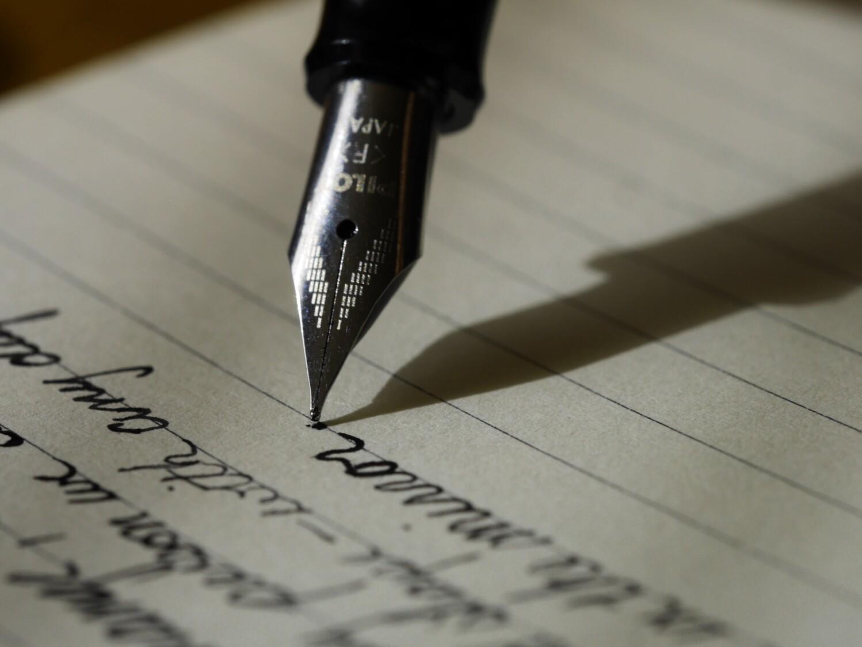 kirjoittava mustekynä ja viivoitettu paperi