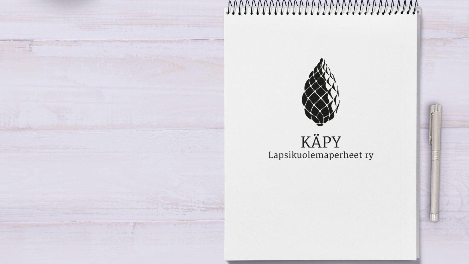 Käpy ry:n logo muistilehtiön päällä, vieressä kynä