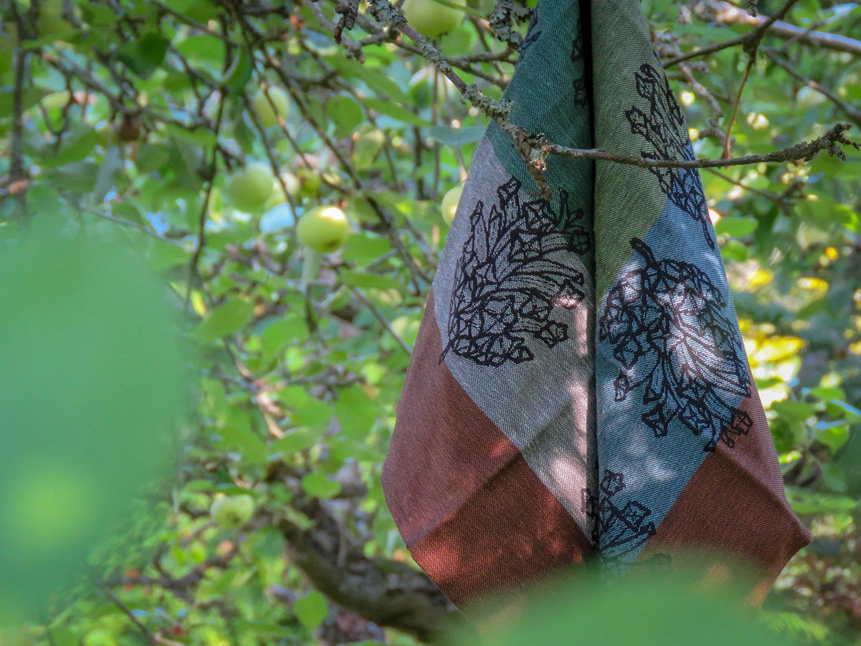 Pellavainen pyyheliina, jossa on punaista, vihreää, sinistä ja harmaata sekä isoja painokuvia kävyistä.