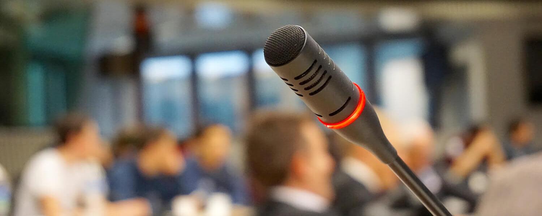 Mikrofoni ja taustalla ihmisjoukko.